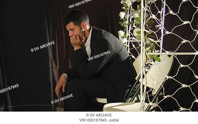 A groom sits in a folding chair under a flower arch