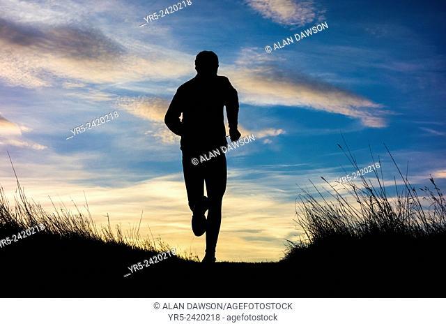 Mature man running uphill on woodland trail at sunrise. Billingham, north east England, United Kingdom