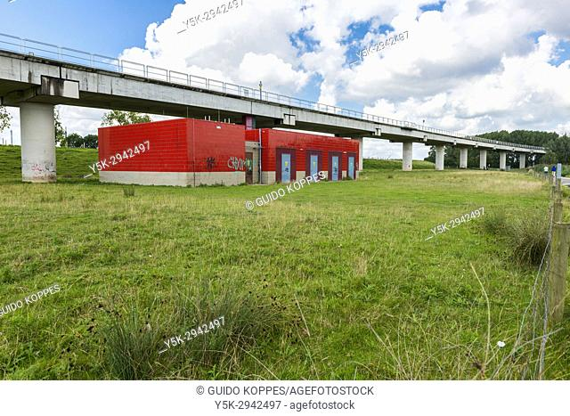 Poortugaal, Netherlands. Electrical transformation building for subway power beneith an elevated subway track and high line