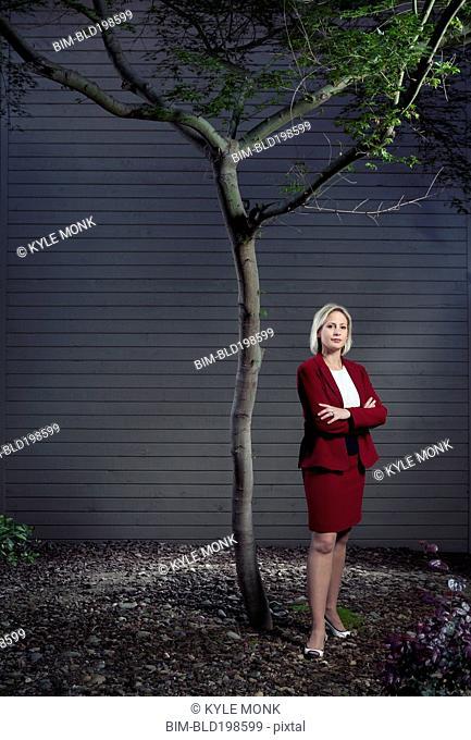 Caucasian businesswoman standing underneath tree