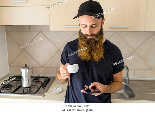 Bearded man standing in kitchen with espresso cup looking at cell phone