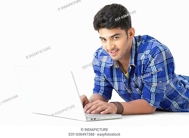 Happy Indian man lying on floor using a laptop PC looking at camera