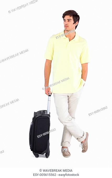 Thoughtful man standing with his suitcase