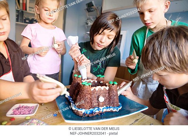 Children decorating cake