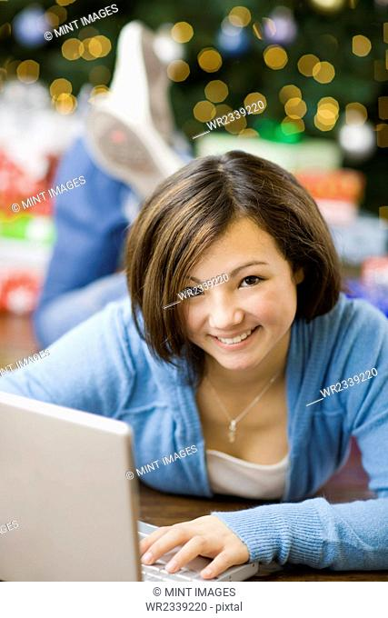 A girl lying on her tummy using a laptop computer by a Christmas tree