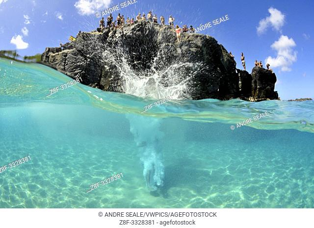 Cliff diver plunges into clear waters of Waimea Bay in the summer, North Shore, Oahu, Hawaii, USA