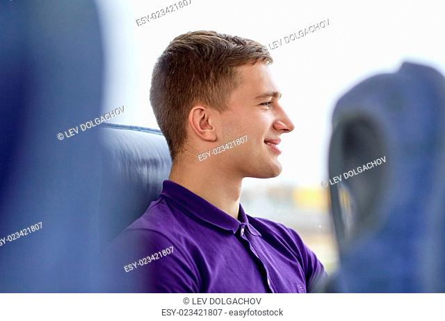 transport, tourism, road trip and people concept - happy young man sitting in travel bus or train and looking through window