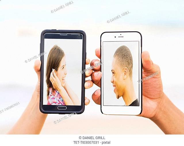 Hands holding smart phones with pictures of young people