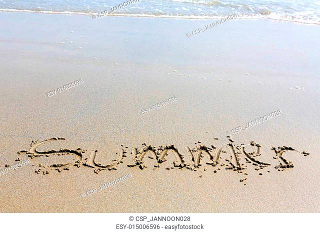 Summer handwritten inscription in sand on a beach