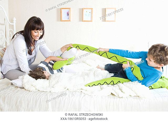 mother playing with children in bed