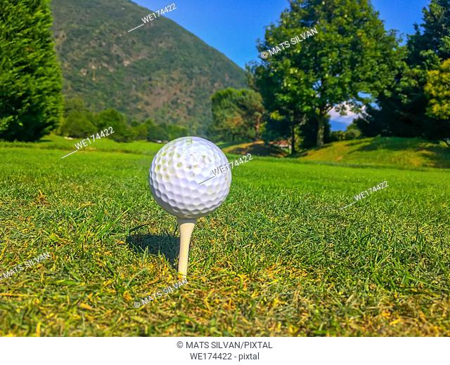 Golf Ball on Tee on the Fairway with Trees and Mountain in Switzerland