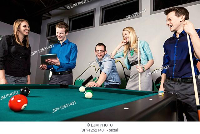 A group of young millennial business professionals playing a game of pool together on a work break; Sherwood Park, Alberta, Canada