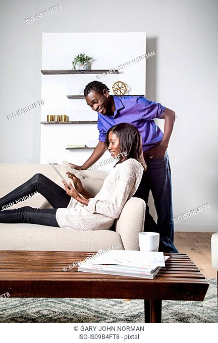 Young woman relaxing on sofa, using digital tablet, young man leaning on sofa