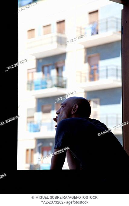 Silhouette on Man Smoking Out of Window in Cagliari in Sardinia