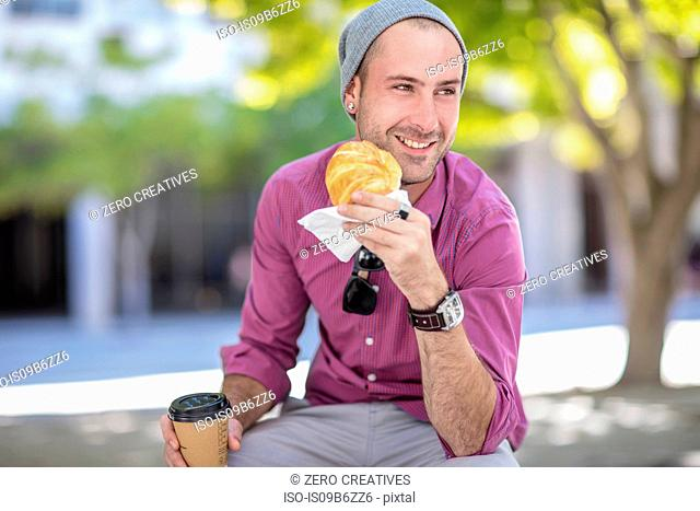 Young man sitting outdoors, holding takeaway coffee cup and croissant