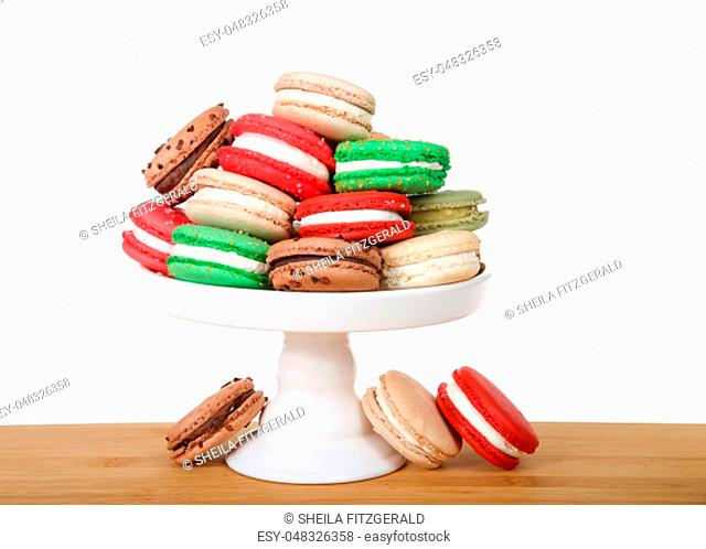 Many Christmas holiday style macaron cookies stacked on a pedestal and laying on wood table isolated on white. Minimalist design