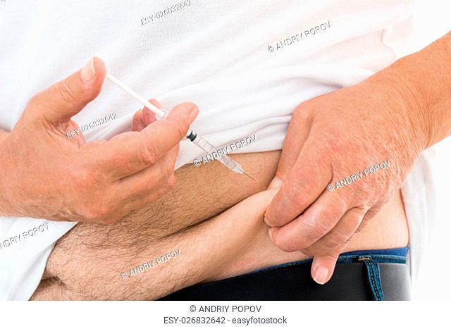Close-up Of A Diabetic Man Injecting Stomach