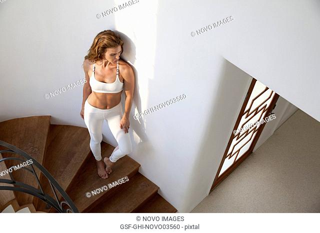 Full-Length Portrait of Mid-Adult Woman in Fitness Attire Standing on Stairs, High Angle View