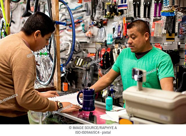 Mechanic and customer in bicycle shop