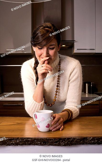 Smiling Woman with Cup with Pink Hearts in Kitchen
