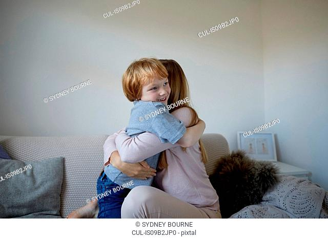 Mid adult woman and son hugging on sofa