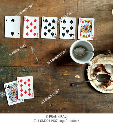 Old dirty table with playing cards and coffee cup