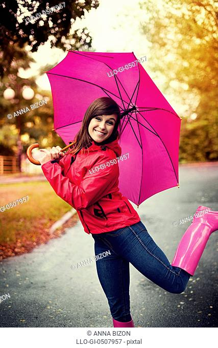 Happy woman with pink umbrella and rubber boots Debica, Poland