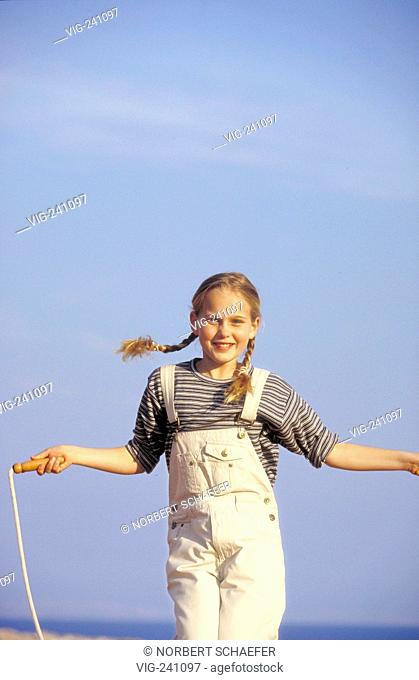 girl with blond plaits, 9 years, wearing blue-white striped t-shirt and short white shorts with flap is skipping rope at the beach under the bue sky  - GERMANY