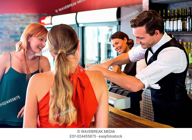 Friends standing at counter while bartender preparing a drink