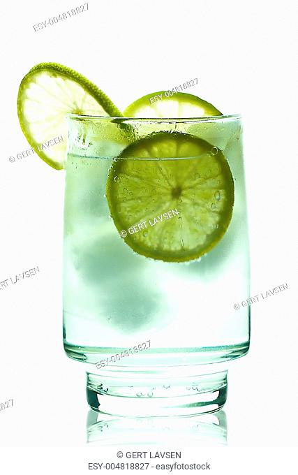 Glass of gin and tonic with ice cubes and lime slices