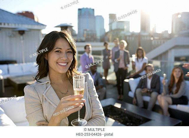 Portrait smiling businesswoman drinking champagne on urban rooftop