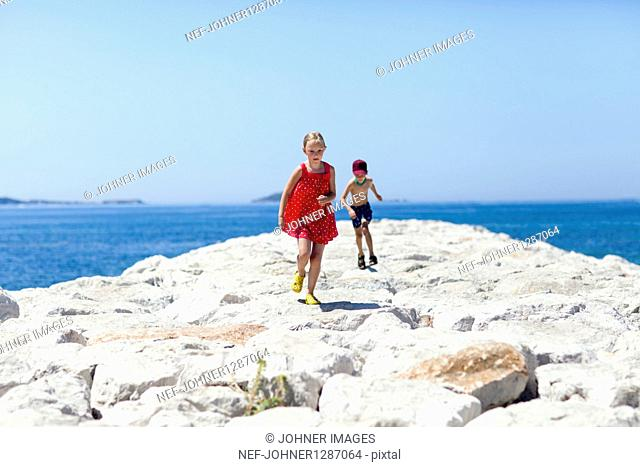 Boy and girl running on stone pier