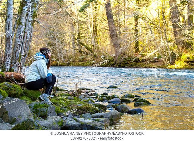 A female hiker takes a rest and looks out over the water of the McKenzie River in Oregon