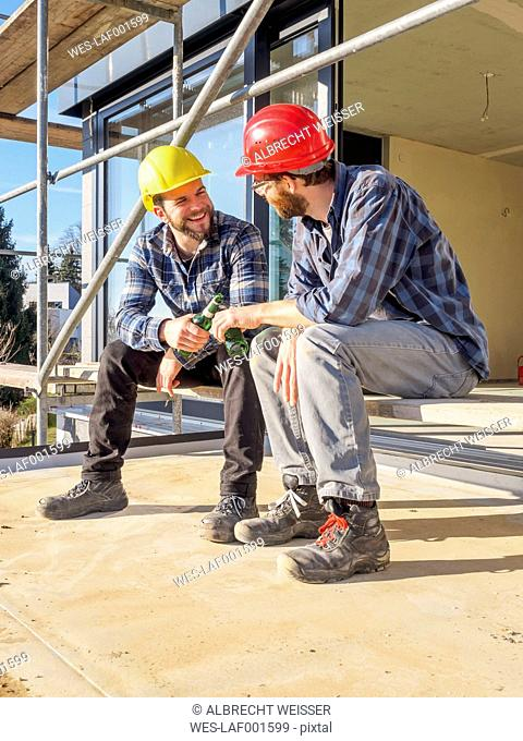 Two craftsmen clinking beer bottles in construction site