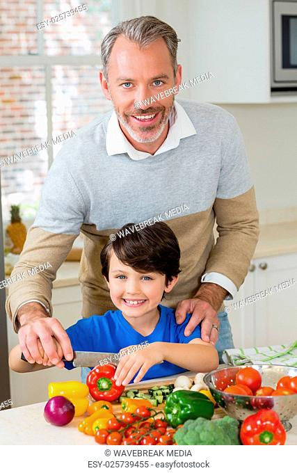 Father assisting a son to chop the red bell pepper in kitchen