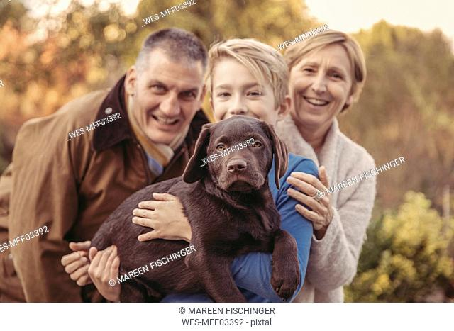 Portrait of family with Labrador Retriever