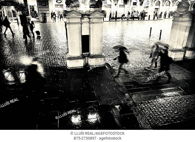 Entrance of a train station at night, rain, pedestrians with umbrellas. Charing Cross, London, England