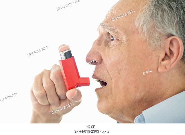 Senior man using inhaler