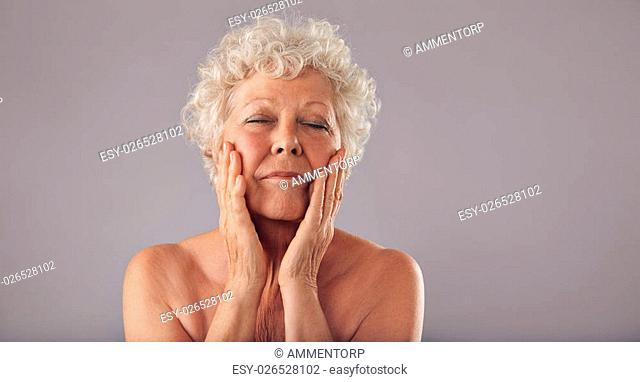 Portrait of senior woman pampering her face against grey background. Natural woman touching her face