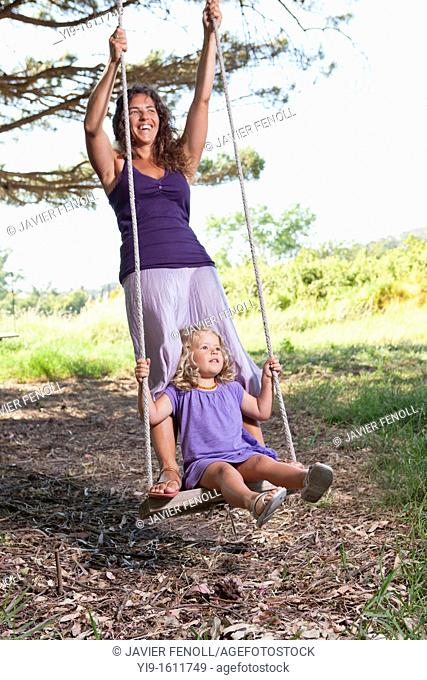 mother and daughter swinging
