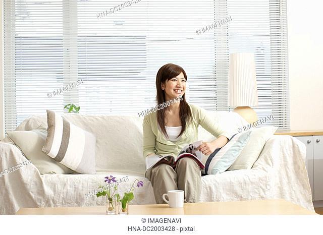 Woman on Sofa Reading a Magazine