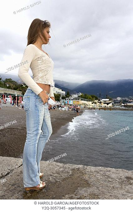 Sexy woman in jeans and small T-shirt showing her abs on the beaches of Yalta, Crimea