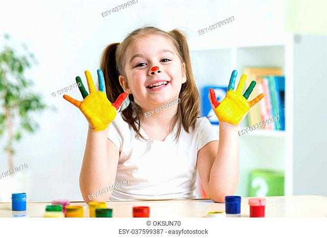 cute child girl with paintied hands by color paints