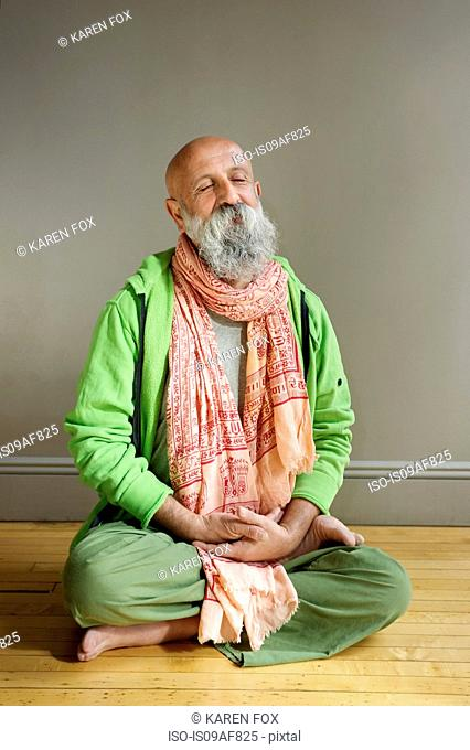 Portrait of senior man sitting in lotus position on floor