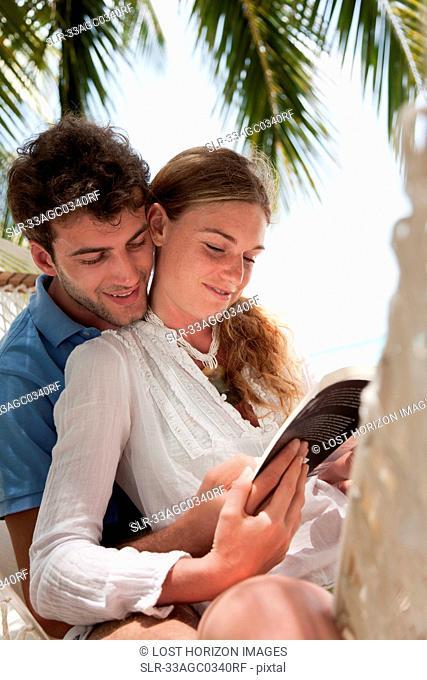 Couple reading in hammock on beach