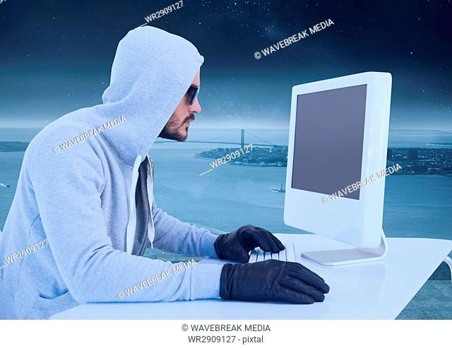Criminal Man in hood on computer in front of landscape