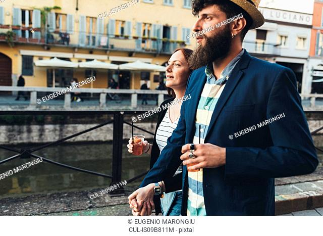 Couple with cocktails strolling along city canal