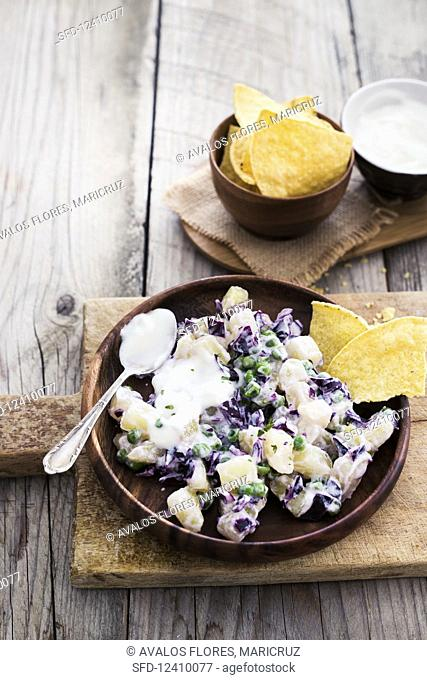Potato salad with red cabbage, peas and sour cream