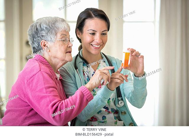 Smiling nurse explaining medicine patient in home