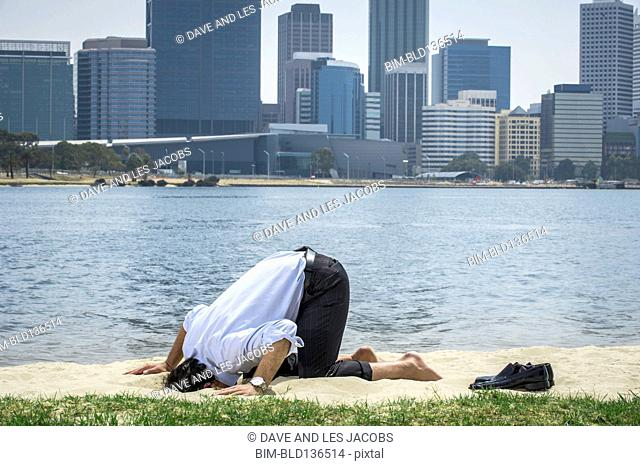Hispanic businessman burying his head in sand on beach, Perth, Western Australia, Australia